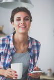 Portret van jonge vrouw die mobiele telefoon thuis met behulp van terwijl het hebben van ontbijt in keuken Stock Foto's