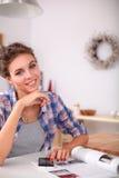 Portret van jonge vrouw die mobiele telefoon thuis met behulp van terwijl het hebben van ontbijt in keuken Stock Afbeelding
