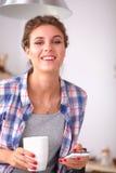 Portret van jonge vrouw die mobiele telefoon thuis met behulp van terwijl het hebben van ontbijt in keuken Royalty-vrije Stock Foto