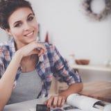 Portret van jonge vrouw die mobiele telefoon thuis met behulp van terwijl het hebben van ontbijt in keuken Stock Afbeeldingen