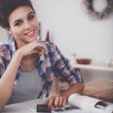 Portret van jonge vrouw die mobiele telefoon thuis met behulp van terwijl het hebben van ontbijt in keuken Royalty-vrije Stock Afbeelding