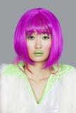 Portret van jonge vrouw die roze pruik over grijze achtergrond dragen Stock Afbeeldingen