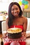 Portret van Jonge Vrouw die uit Kaars op Verjaardagscake blazen Stock Foto's