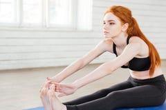 Portret van jonge vrouw die uitrekkende oefening doen stock foto's
