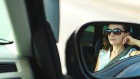 Portret van jonge vrouw in een achteruitkijkspiegel stock footage