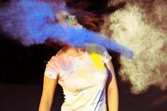 Portret van jonge vrouw met blazend droog kleurrijk binnen poeder Holi Stock Fotografie