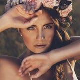 Portret van jonge vrouw met circlet van bloemen op hoofd stock afbeelding