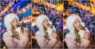 Portret van jonge vrouw met het lange eerlijke haar stellen openlucht in koude de winteravond Mooi blonde die een grote lolly hou Stock Afbeeldingen