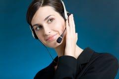 Portret van jonge vrouw met hoofdtelefoon, op blauwe achtergrond, het glimlachen Royalty-vrije Stock Afbeelding