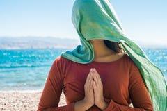 Portret van jonge vrouw met lange groene sjaal op hoofd op het strand met overzeese achtergrond Stock Afbeelding
