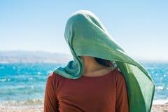 Portret van jonge vrouw met lange groene sjaal op hoofd op het strand met overzeese achtergrond stock afbeeldingen