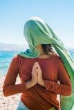 Portret van jonge vrouw met lange groene sjaal op hoofd op het strand met overzeese achtergrond Royalty-vrije Stock Fotografie