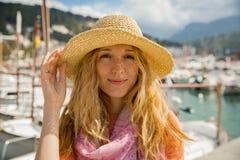 Portret van jonge vrouw met licht krullend haar in strohoed stock fotografie