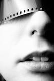 Portret van Jonge Vrouw met 35mm Film over Haar Ogen Royalty-vrije Stock Foto's