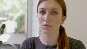 Portret van jonge vrouw met paardestaartzitting in koffie en het kijken in camera, ernstig en bepaald stock videobeelden