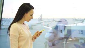 Portret van jonge vrouw met smartphone in internationale luchthaven Luchtvaartlijnpassagier in een luchthavenzitkamer die wachten stock footage