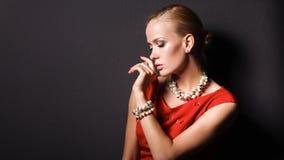 Portret van jonge vrouw op rode kleding, zwarte achtergrond Stock Fotografie