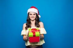 Portret van jonge vrouw in santahoed met giftdoos op blauwe achtergrond royalty-vrije stock fotografie