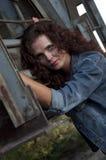 Portret van jonge vrouw tegen de bouw van het grungemetaal Royalty-vrije Stock Afbeeldingen