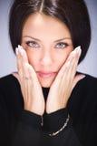 Portret van jonge vrouw wat betreft haar gezicht Stock Afbeeldingen