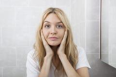 Portret van jonge vrouw wat betreft wangen in badkamers Royalty-vrije Stock Afbeeldingen