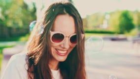Portret van jonge vrouw in zonnebril die bellen in openlucht blazen en pret hebben op Cinematic langzame motie, jong festival stock video