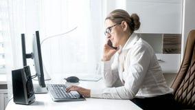Portret van jonge vrouwelijke chef- zitting achter bureau en het spreken telefonisch royalty-vrije stock afbeeldingen