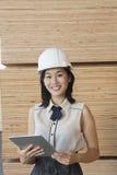 Portret van jonge vrouwelijke fabrieksarbeider die tabletpc met houten planken op achtergrond met behulp van Royalty-vrije Stock Afbeelding