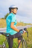 Portret van jonge vrouwelijke Kaukasische fietseratleet op fiets Ha Stock Foto's