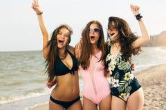 Portret van jonge vrouwelijke vrienden die pret op de overzeese kust hebben die camera het lachen bekijken Het mooie gelooide vro royalty-vrije stock fotografie