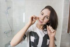 Portret van jonge vrouwen flossing tanden in badkamers Stock Afbeeldingen