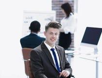Portret van jonge werknemers die dichtbij de Desktop zitten stock afbeeldingen