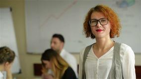 Portret van jonge witte vrouw in een bezige moderne werkplaats stock footage