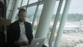 Portret van jonge zakenman die een e-mail op zijn laptop in de luchthaven typt stock video