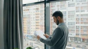 Portret van jonge zakenman die financieel onderzoek lezen dichtbij venster in modern bureau stock footage