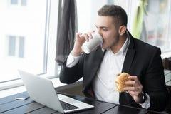 Portret van jonge zakenman die op zijn lunchtijd werken in moder Stock Foto's