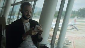 Portret van jonge zakenman die zijn smartphone in de luchthaven gebruikt stock footage