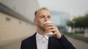 Portret van jonge zakenman met koffie die de camera onderzoeken en hete drank drinken Het lachen vrolijk portret van stock videobeelden