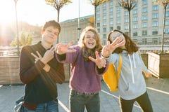 Portret van jongen van de vriendentiener en twee meisjes die, makend grappige gezichten, die overwinningsteken in de straat tonen stock afbeeldingen