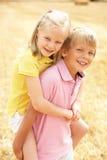 Portret van Jongen en Meisje op de Zomer Geoogst Gebied Stock Fotografie