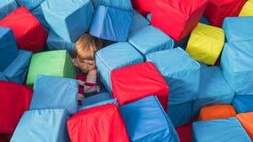 Portret van jongen het spelen met zachte kubussen Jongensslaap op Vermaakcentrum Jong geitje onder plastic kubussen in kinderen stock foto's