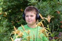Portret van jongen met hoofdtelefoons rond daylily Stock Afbeeldingen
