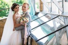 Portret van jonggehuwden op huwelijksdag De bruidegom in een grijs kostuum met een wit overhemd en een vlinderdas koestert een mo stock afbeeldingen