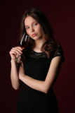 Portret van juffrouw met wijnglas Sluit omhoog Donkerrode achtergrond stock foto's