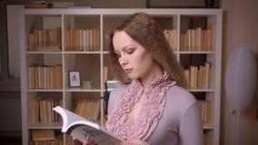 Portret van Kaukasisch wavy-haired de lezingsboek dat van de blondeleraar aandachtig en concentreert is zich dat bij bibliotheek stock video