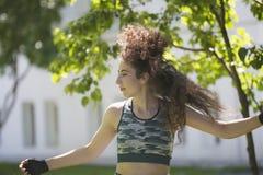 Portret van Kaukasische jonge vrouw met lange krullende haartraining in het park bij zonnige dag stock afbeelding