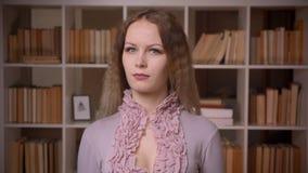Portret van Kaukasische wavy-haired blondeleraar die thoughful bij bibliotheek zijn stock video