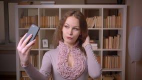 Portret van Kaukasische wavy-haired blondeleraar die verleidelijke selfiefoto's maken in camera bij bibliotheek stock videobeelden