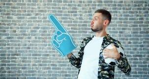 Portret van kerel met voetbal en schuim de ventilator van handsporten ondersteunend favoriet team stock video