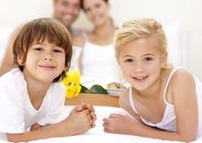 Portret van kinderen in bed met hun ouders Stock Afbeeldingen